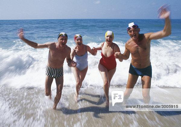 Zwei ausgelassene Seniorenpaare im Meer