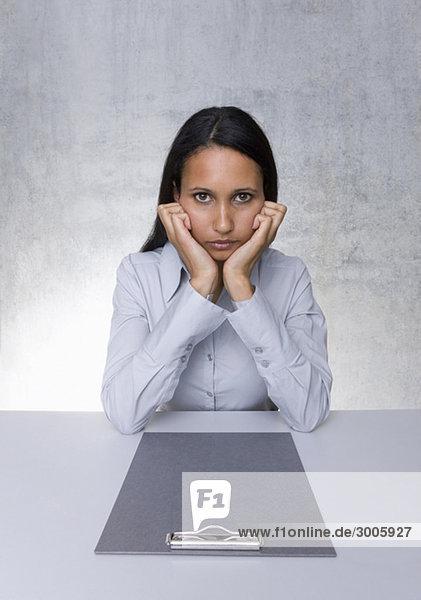 Frau sitzt mit leerem Klemmbrett an Tisch