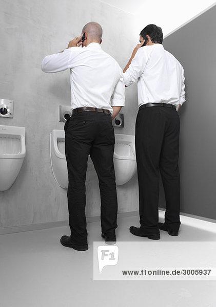 Zwei Geschäftsmänner an Pissoir mit Handys
