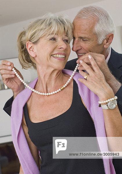 Senior legt seiner Frau eine Perlenkette um