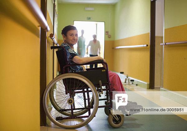 Seniorin sitzt im Rollstuhl in einem Altersheim