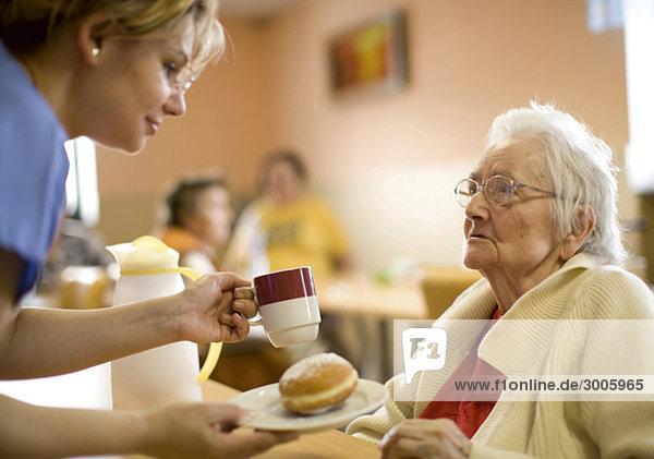 Pflegerin mit Seniorin in Altenheim
