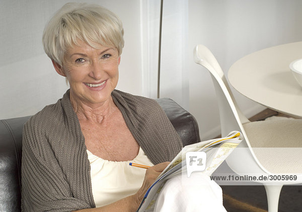 Seniorin sitzt mit Kreuzworträtsel auf Sofa Seniorin sitzt mit Kreuzworträtsel auf Sofa