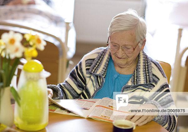 Seniorin liest Zeitschrift in Altenheim