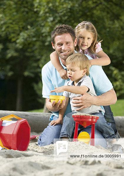 Vater mit zwei Kindern beim Spielen in Sandkasten