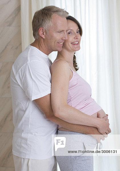Mann umarmt schwangere Frau
