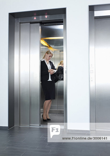 Geschäftsfrau steht in Aufzug und sieht auf Uhr
