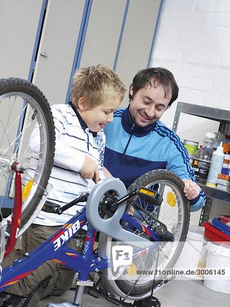 Vater und Sohn reparieren Fahrrad