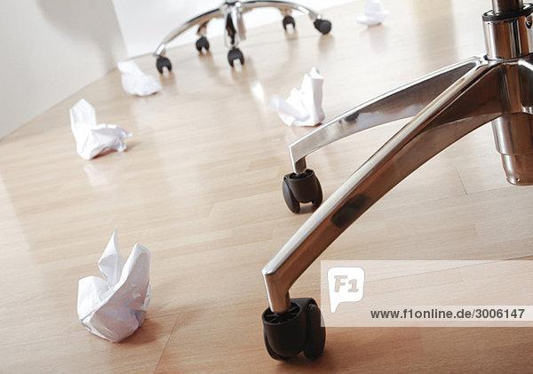 Papierknäuel liegen neben Stuhlbeinen am Boden Papierknäuel liegen neben Stuhlbeinen am Boden