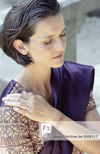 Dunkelhaarige Frau in einem Sari legt eine Henna bemalte Hand auf ihre Schulter - Meditation - Brauchtum