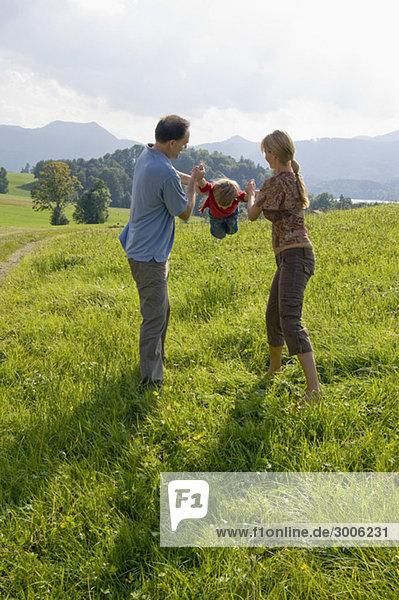 Familie spielt auf einer Wiese  Gmund  Bayern  Deutschland
