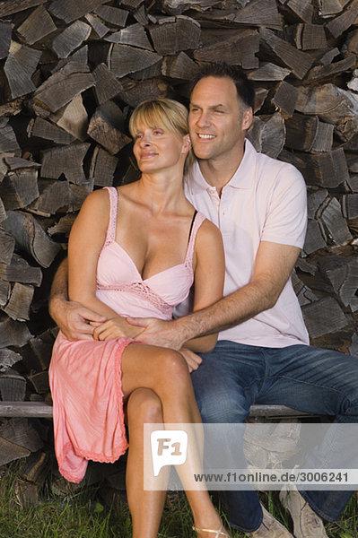 Paar sitzt vor einem Holzstapel  Gmund  Bayern  Deutschland