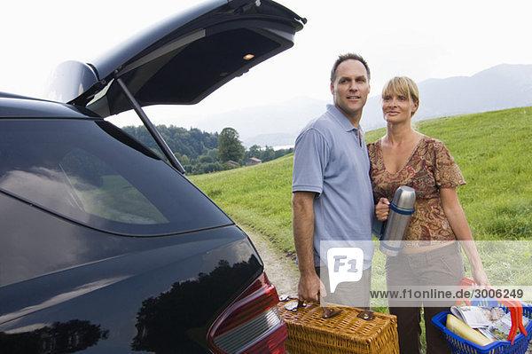 Paar mit Picknickkorb am Auto  Gmund  Bayern  Deutschland