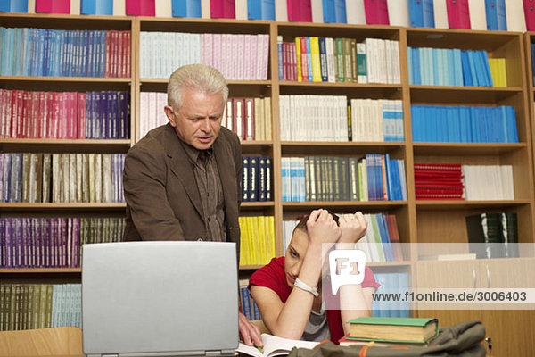 Professor steht neben Studentin