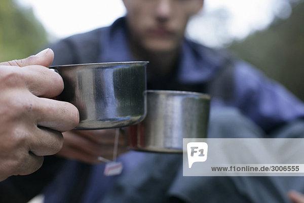 Zwei Männer stoßen mit metallischen Tassen an - Heißgetränk