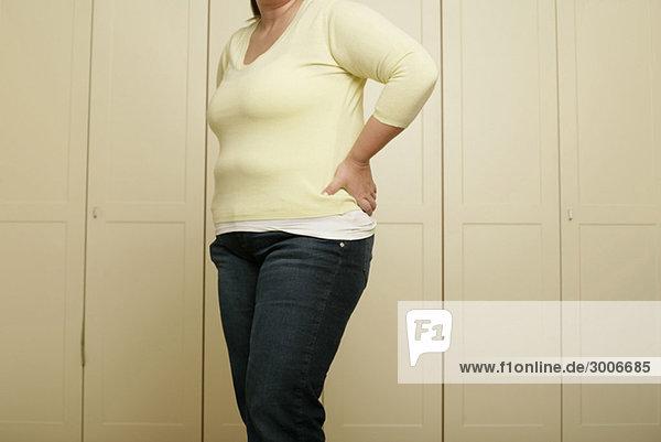 Vollschlanke Frau steht vor einem Wandschrank - Übergewicht