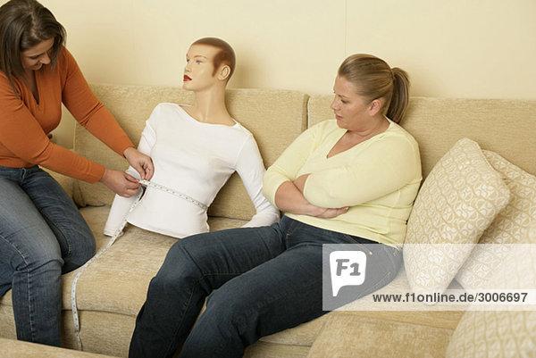 Zwei vollschlanke Freundinnen messen die Taille einer Schaufensterpuppe - Schönheitsideal - Übergewicht