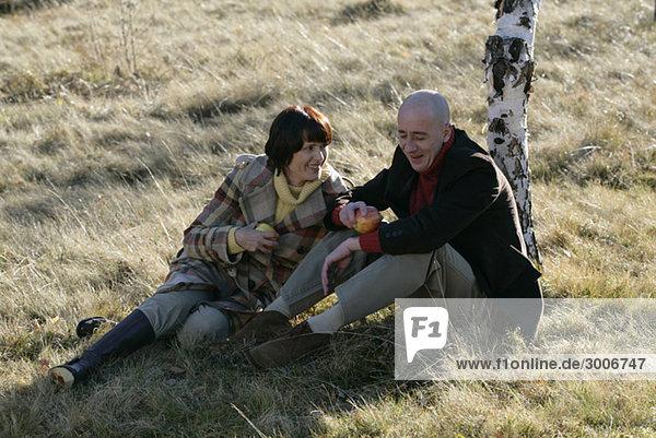Älteres Paar sitzt auf Rasen und hält Obst in den Händen