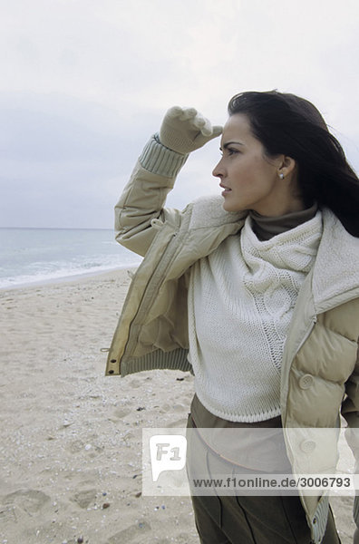 Junge brünette Frau hält Ausschau - Winterbekleidung - Jahreszeit - Strand