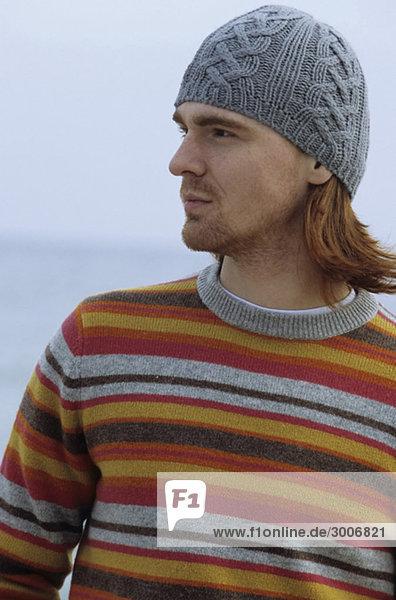 Mann mittleren Alters mit Wollmütze und gestreiftem Pullover - Winterbekleidung