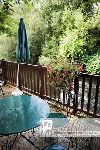 Möbel und ein Sonnenschirm auf einer Veranda in einem Restaurant in Frankreich