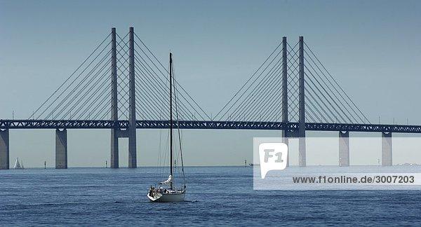 Boot im Meer mit einer Hängebrücke im Hintergrund  Öresund Link  Malmö  Schweden