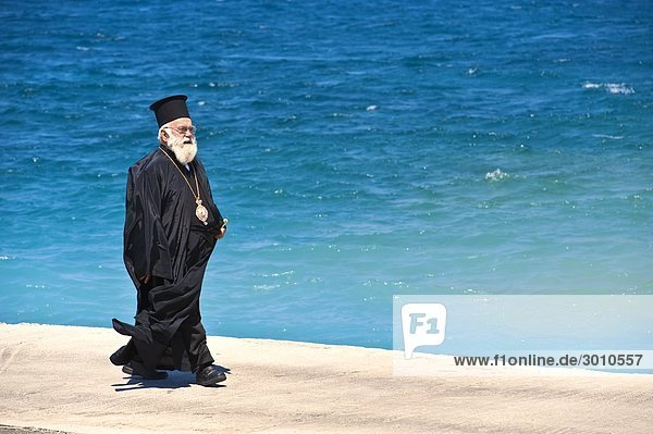 Orthodoxer Priester geht Uferpromenade entlang  Kalymnos  Griechenland