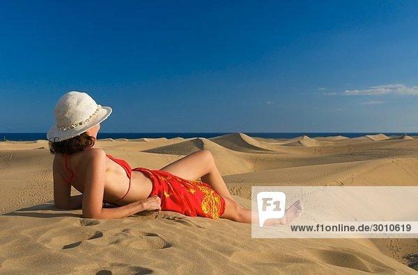 Frau liegt auf einer Sandüne und schaut auf das Meer  Maspalomas  Gran Canaria  Spanien  Seitenansicht