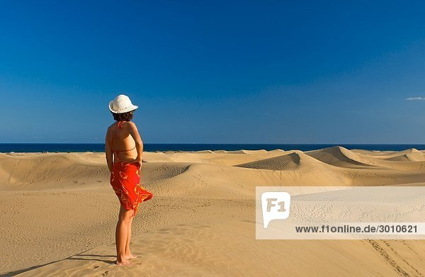 Frau auf einer Sandüne schaut auf das Meer  Maspalomas  Gran Canaria  Spanien  Rückansicht