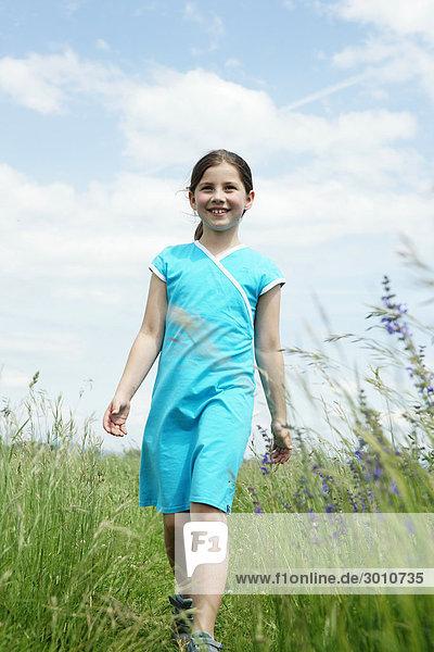Mädchen geht durch eine Wiese  Flachwinkelansicht  Frontal