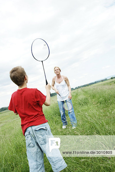 Mother and son playing badminton on a meadow