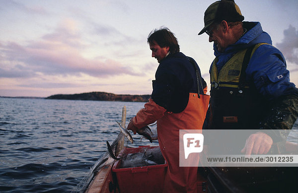 Männer stehen auf Boot in der Seitenansicht Ozean