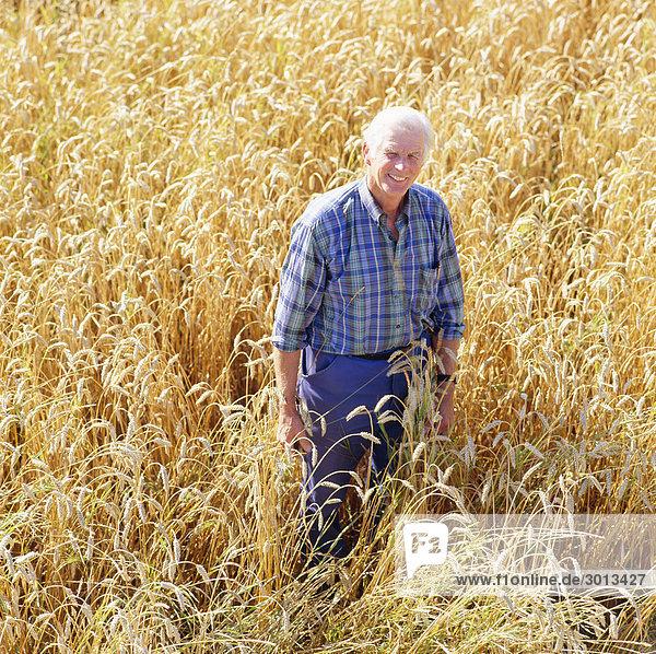 Senior man standing in field