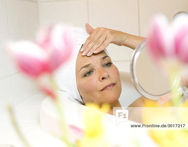 Frau liegt in einer Badewanne und betrachtet sich im Handspiegel  Close-up