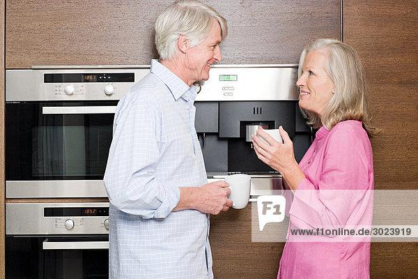 Mittelalterliches Paar in der Küche stehend mit Tassen Kaffee