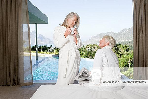 Mittelalterliches Paar mit Bad im Schlafzimmer mit Blick auf den Swimmingpool