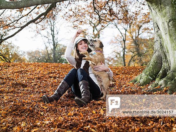Frau spielt mit Hund im Wald