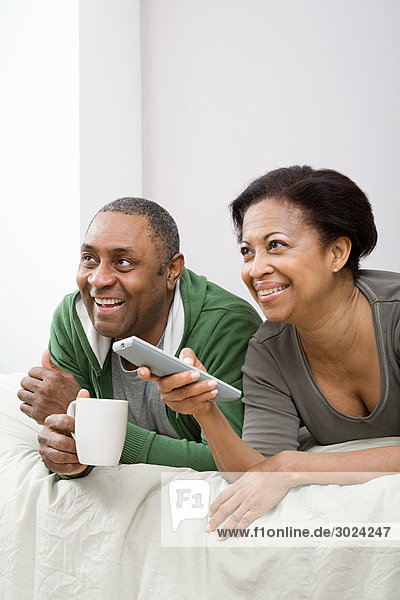 Couple watching television on bed