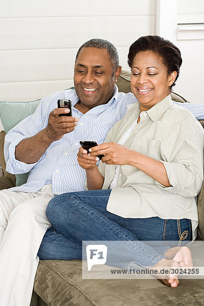Reife Paare mit Mobiltelefonen