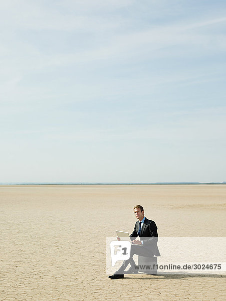 Businessman sitting on a briefcase in the desert
