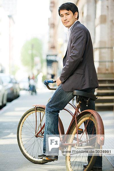 Männlicher Büroangestellter auf dem Fahrrad