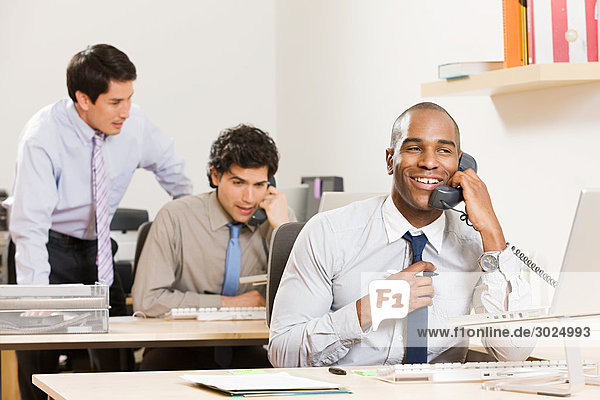 Three male office workers at their desks