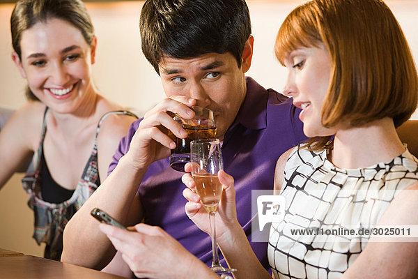 Drei Freunde  die in einer Bar trinken.