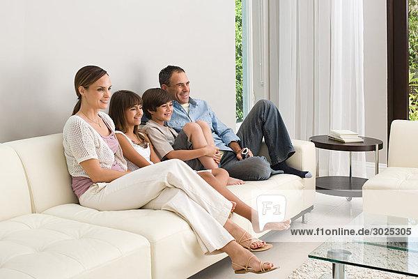 Familie entspannt auf dem Sofa