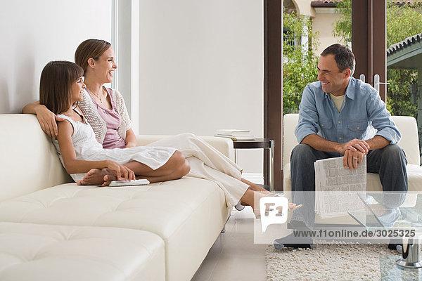 Familie im Wohnzimmer sitzend