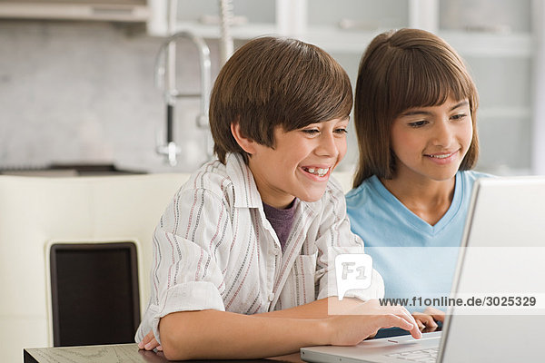 Brother and sister using a laptop computer