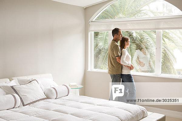 Paar mit Blick aus dem Schlafzimmerfenster