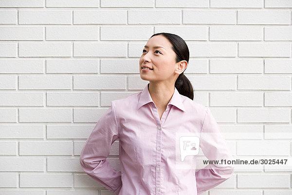Japanerin an einer Wand stehend