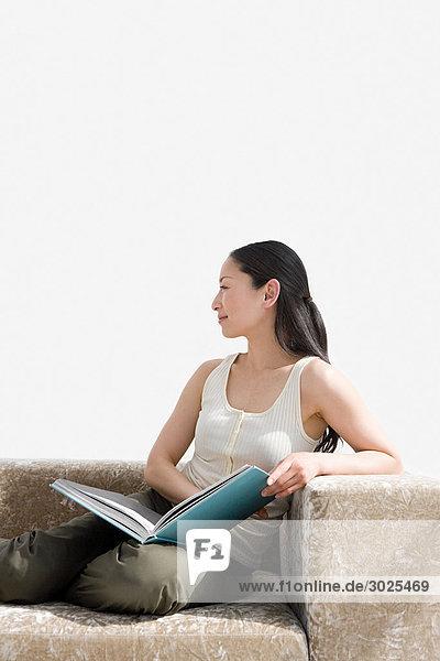 Frau beim Lesen eines Buches auf dem Sofa