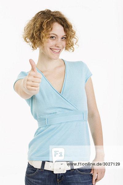 Junge Frau  Daumen hoch  lächelnd  Porträt